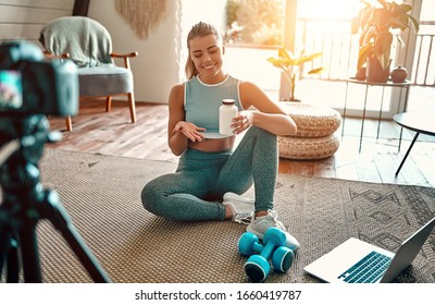 Woman blogger in sportswear sitting on the floor with dumbbells and a laptop and showing a jar of sports nutrition proteins to the camera at home in the living room. Sport and recreation concept.