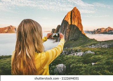 Woman blogger taking photo by smartphone exploring sunset mountains in Norway adventure trip summer vacations traveling lifestyle modern technology