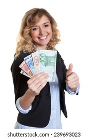 Woman with blond hair showing money and thumb