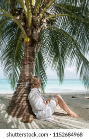 Woman with blond hair and a white dress and bare legs leaning against a palm tree and looking at the sea. Next to her is a coconut with inscription: do not disturb (portrait orientation)