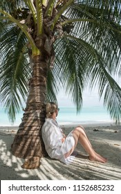 Woman with blond hair and a white dress and bare legs leaning against a palm tree and looking at the sea. Next to her is a coconut with inscription: do not disturb. Portrait orientation