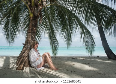 Woman with blond hair and a white dress and bare legs leaning against a palm tree and looking at the sea. Next to her is a coconut with inscription: do not disturb. Landscape orientation