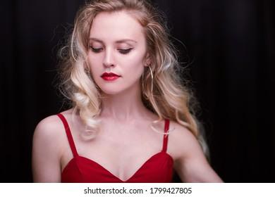 Weibliche Blondine in rotem Kleid und roten Lippen. Auf schwarzem Hintergrund