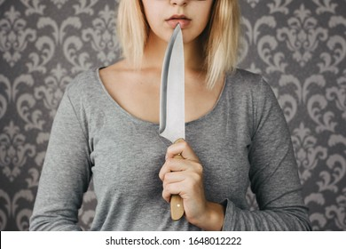 woman blonde holding a kitchen knife in her hand, threat, murder, domestic violence