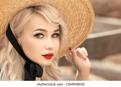 Woman blonde in straw hat close up portrait.