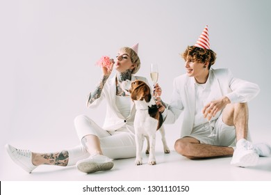 woman blowing in blower while man holding glasses with champagne while sitting near beagle dog on grey background