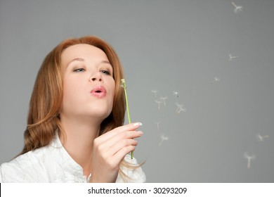 woman blowing at dandelion
