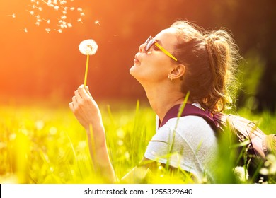 woman blowing a dandelion in a green field during the summer