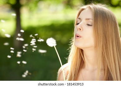 Woman blowing dandelion over green background outdoors, wish concept