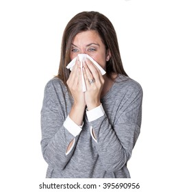 Woman blowing her nose hard with a tissue