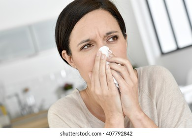 Woman blowing her nose, having allergy