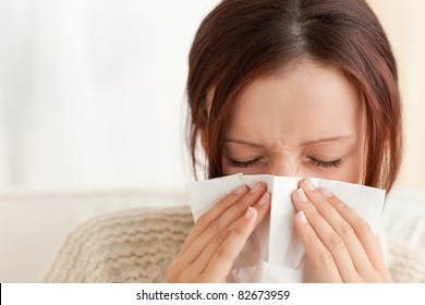 Woman blowing her nose in a living room