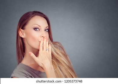 Woman blowing a kiss puckered lips covering mouth with hand looking at you camera. Girl with long hair woman amazed isolated on gray grey horizontal studio wall Background Expressive facial expression