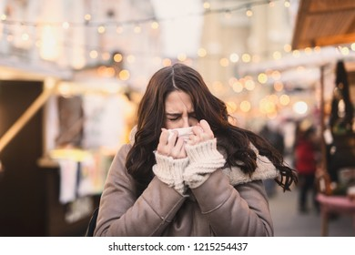Woman blowing nose while standing on the street on cold weather.