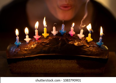 woman is blowing out some colorful candles on a marble cake