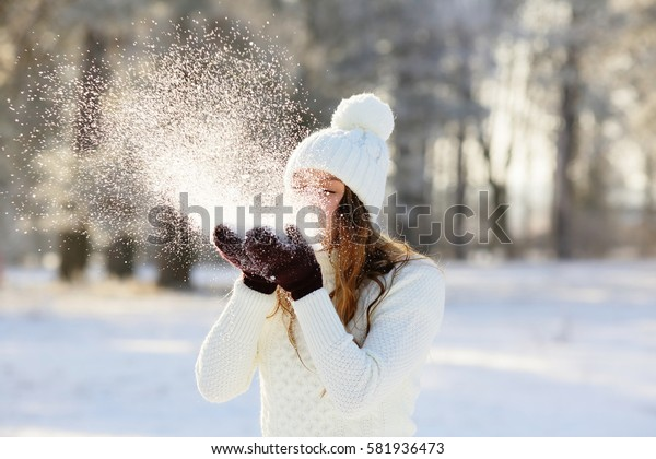 Woman blowing in the snow in his hands, outdoors in winter