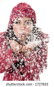 Woman blowing soft white flakes.  Focus on woman, flakes are  in motion.