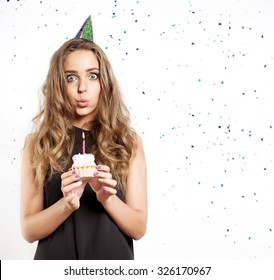 Woman blows out the candles on a birthday cake