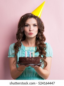 Woman blows out the candles on a birthday cake.