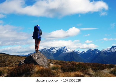 Woman with a blue backpack and shorts standing on rock and looking on beautiful mountains with snow around. Grassy area around rock. Blue sky with some clouds. Summer, Kepler track,nz