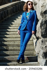 woman in blue business suit and sunglasses poising on a stone stairs