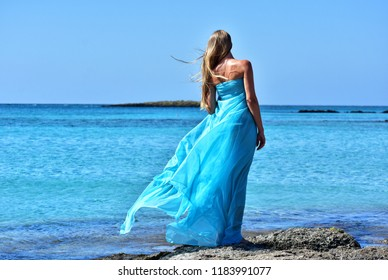 woman in blue chiffon dress on elafonisi beach on crete island in greece