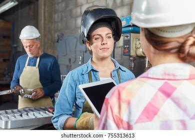 Woman as blue collar worker in metallurgy workshop
