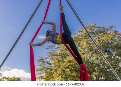 Woman in blue dance does a vertical split on red ribbon
