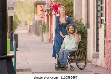 Woman in blue dress with friend in wheelchair on sidewalk