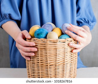 Woman in the blue dress holding the basket with colored yellow easter eggs
