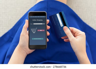 woman in a blue dress holding a phone with online shopping on the screen and credit card