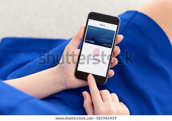 woman in blue dress holding phone with debit card and app touch pay on screen