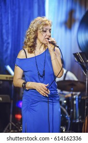A woman in a blue dress is singing on stage. A woman of European appearance, middle-aged acts in a restaurant.