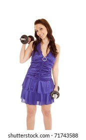 A woman in a blue dress is smiling and working out.