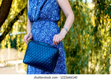 A woman in a blue dress is standing against a background of nature and holding a leather bag. The modern concept of fashion and life style.