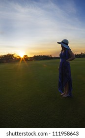A woman with a blue dress and sun hat standing on a green field of grass watching the sun set. Sun has a flair and sky has wispy clouds.