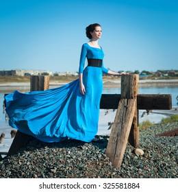 Woman in blue dress walks outdoors, summer day