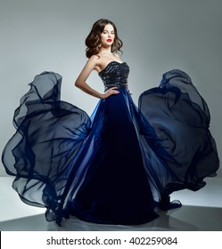 Woman in blue evening dress flying on wind. Young beauty woman in waving dress. Dancer in silk dress.