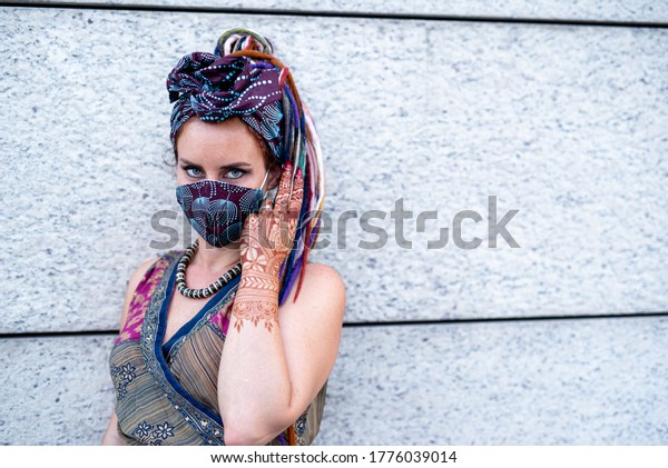 woman with blue eyes, mysterious fashion masquerade, handmade protective masks for coronavirus used in gypsy fashion style