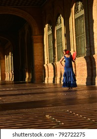 The woman with the blue flamenco dress and the red fan