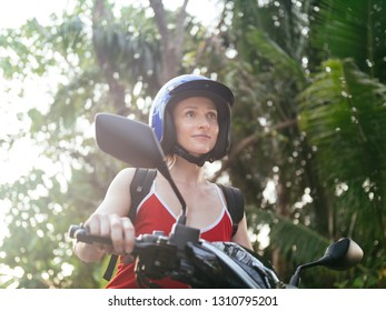 Woman in blue helmet riding scooter motorbike on the jungle road with palm trees. Tropical travel and transport