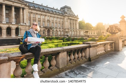 A woman in a blue jacket with a backpack and a map sits on the parapet against the background of the main attraction of Brussels - the Royal Palace and looks up, Belgium