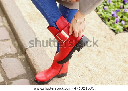 9e5f19d82ae4 Woman in blue jeans and gray coat walking on the city street. Girl in  bright red leather ankle boots near the flower bead. - Image