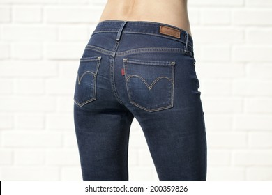 Woman in blue jeans with naked back isolated on white brick wall