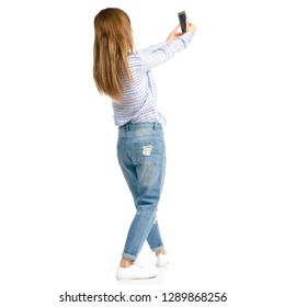 Woman in blue jeans and shirt smartphone selfie on white background isolation, back view