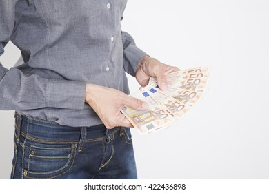 woman blue jeans trousers and grey shirt counting currency money cash fifty Euro banknotes in her hands isolated over white background