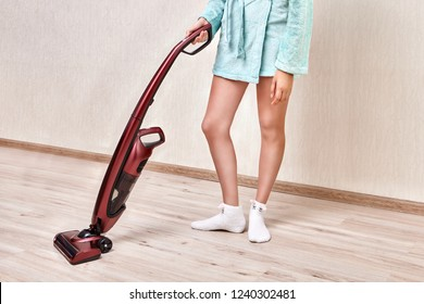 A woman in a blue robe cleans dust in an empty room with a laminated floor using a handheld vacuum cleaner.