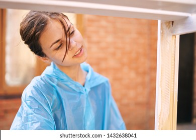 woman in a blue robe paints the wall at home