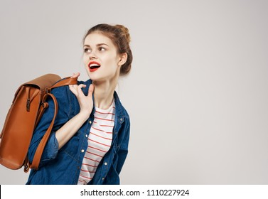 a woman in a blue shirt and with a brown backpack looked back