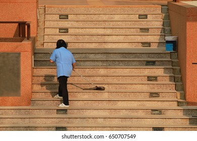woman in blue shirt cleaning outdoor staircase with mop.
